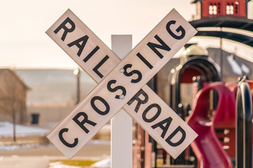 A Railroad Crossing sign with playground background