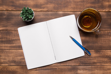 top view image of open notebook with blank pages next to cup of coffee on wooden table. ready for adding text or mockup.