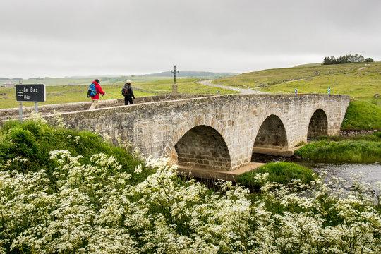 Two hikers cross a bridge in the Aubrac region on the pilgrimage way to santiago de Compostela