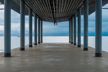 Pier under a canopy, a view of the sea and the gloomy autumn sky