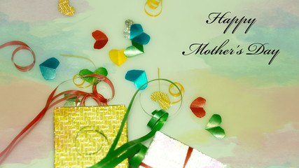 Happy Mother's Day words with Colourful heart shape ribbon and small gift boxes on colorful bokeh, flare background. Image noise and light