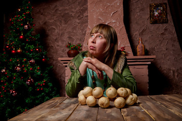 Girl siting near the table with a bunch of onions in room with red walls