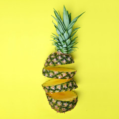 Sliced fresh tropical fruit pineapple on yellow background.