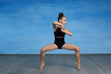 Girl athlete doing exercise gymnastics  squatting on  half toes, legs are spread wide apart, hands are in the lock. , looking  away on a blue background.