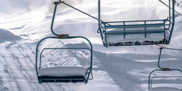 Empty ski lifts with sunlit snow in the background