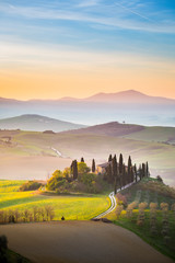 A lonely farmhouse between tuscan rolling hills. Val d'Orcia, Siena province, Tuscany, Italy