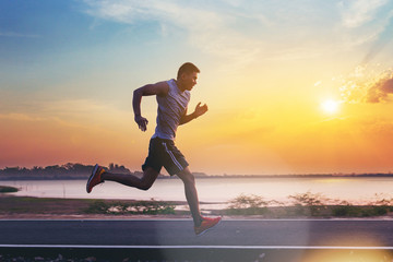 Silhouette of man running sprinting on road. Fit male fitness runner during outdoor workout with sunset background Wall mural