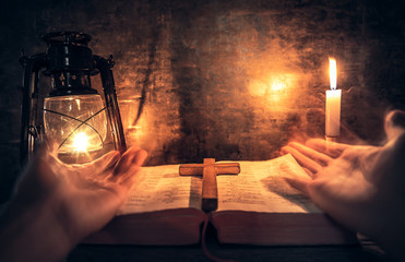 Praying of man in worship room with the cross and bible. christian praying concept.