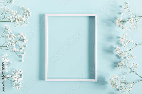 Flowers composition romantic. White gypsophila flowers, photo frame on pastel blue background. Valentine's Day, Easter, Birthday, Happy Women's Day, Mother's day. Flat lay, top view, copy space