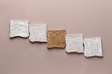 Golden slice of bread among white ones on color background. Concept of uniqueness