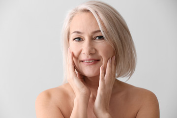 Mature woman giving herself face massage on light background