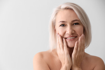 Mature woman giving herself face massage on light background Wall mural