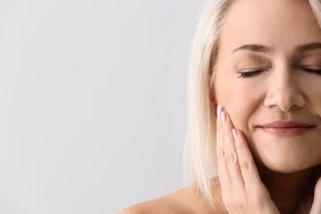Mature woman giving herself face massage on light background