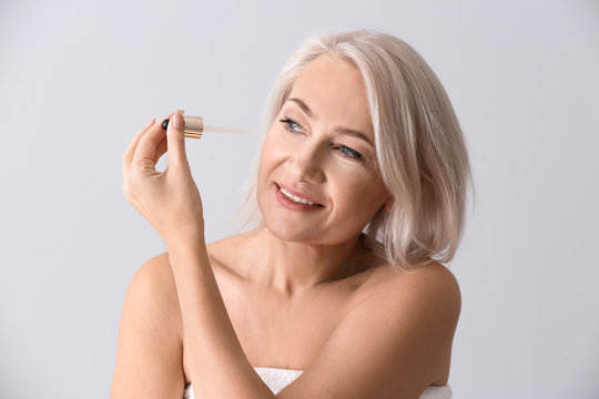 Mature woman applying face serum on light background
