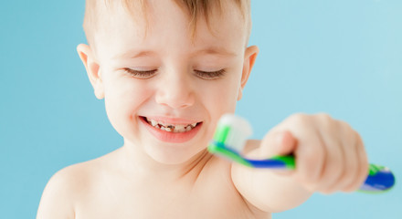 Portrait of little boy with toothbrush on blue background