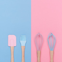 top view of a set of pastel color kitchen utensils on a pastel pink and blue background