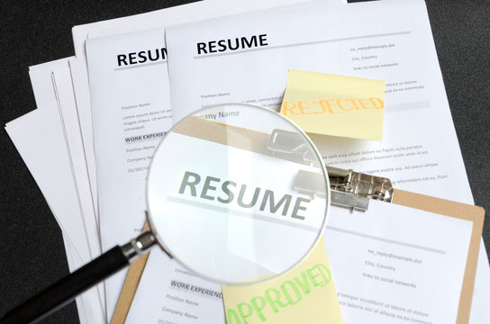 Pile of resume templates and sticks on it, black background. HR made decision and approved one candidate and rejected to another.Process of reviewing resume applications