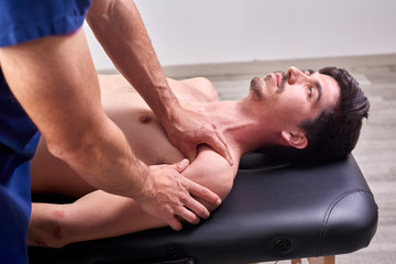 Osteopathy, sports injury rehabilitation concept. A male patient suffering from back pain and a physical therapist. Chiropractic shoulder adjustment. Acupressure.