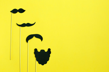 Happy Father's Day with Copy Space. Mustache photo booth props. Mustache cut outs from paper on yellow background .