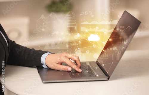 Business woman in homey environment using laptop with cloud