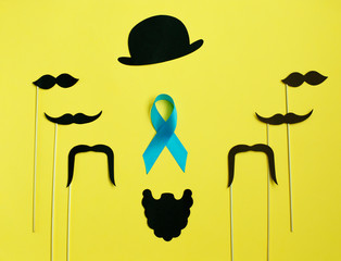 image of a man on paper. Beard and mustache blue ribbon. on yellow background. Concept of prostate cancer