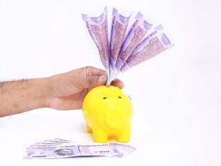 Putting money in piggy bank. Isolated on the white background.