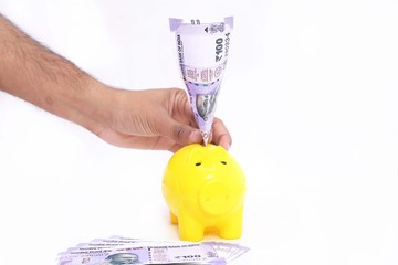 Picture of hand putting money in piggy bank. on the white background.