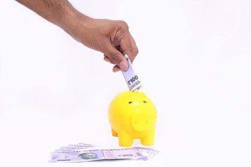 Picture of hand putting money in yellow piggy bank. Isolated on the white background.