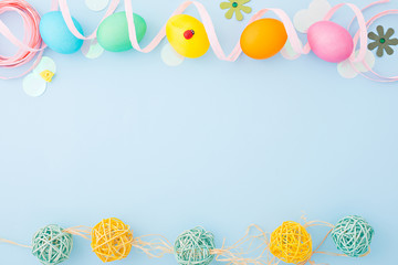 Colorful Easter eggs with decoration on a light blue background. Flat lay. Top view. Copy space