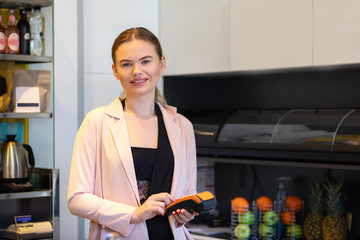 Fruit juice bar owner standing at cash counter holding an electronic card payment machine - Smiling young woman holding wireless terminal machine looking at camera.