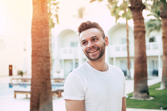 Nodding my head. Utterly good looking man in white t-shirt with a superb smile in front of multicolored background of palm trees, green grass and sky blue swimming pool.