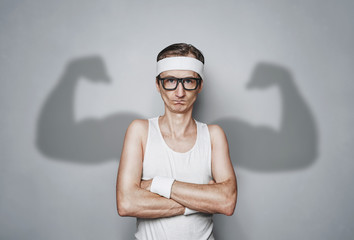 Funny sport nerd with shadow muscle arms over gray wall with copy space