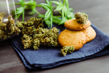 Sweets with cannabis. Cannabis buds on a black background. Sweets with weed. Baking with the addition of CBD. Cookies with marijuana.