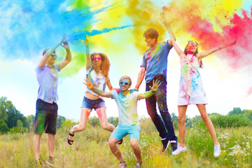 Cheerful and happy friends soiled by bright paints jumping and laugh in colorful smoke on nature. Company of young people having fun with holi paints on spring summer festival. Holi party concept.