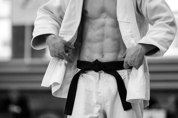 judo athlete in white kimono and black belt black and white photo