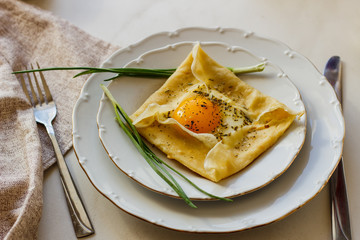 Galette complete. Traditional French crepe with egg, cheese and bow at restaurant. French cuisine.
