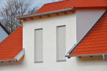 Einfamilienhaus-Neubau mit rotem Ziegeldach, Edelstahl-Abschlussblechen und Beton-Schleppgaube