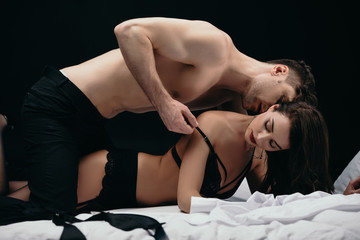 man kissing and undressing beautiful sexy woman isolated on black