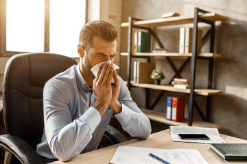 Young handsome businessman sit at table and sneeze in his own office. He cover nose with white napkin. Sick guy suffer.