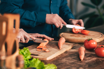 selective focus of couple cutting carrot and tomato in kitchen