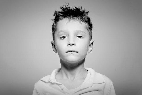 Sad little boy posing in studio