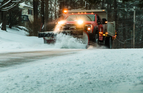 Snow plow at dusk during maintaining road in a winter storm in a residential neighborhood