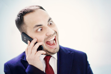 A businessman is making faces during a phone talk.