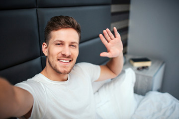 Young man in bed. He hold camera and smile. Guy wave with hand.