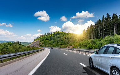 Car driving on highway surrounded by picturesque mountains. Wall mural