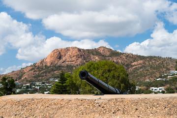 Kanone in Abwehrstellung mit Berg in Wolken im Hintergrund