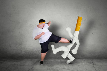 Asian obese man kicking a cigarette