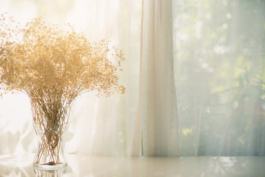 Dried flowers in a vase on a window with morning light. Bouquet of dried flowers in the on table top in house.