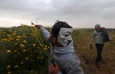 Palestinian demonstrator wearing a mask at the back of his head uses a slingshot to hurl stones at Israeli forces during a protest at the Israel-Gaza border fence, in the southern Gaza Strip
