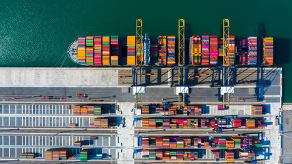 Container cargo freight ship with industry working crane bridge discharge at container terminal, Aerial top view business commercial container cargo ship at deep sea port.